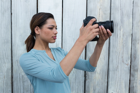 Female photographer reviewing captured photos in her digital camera against wooden background
