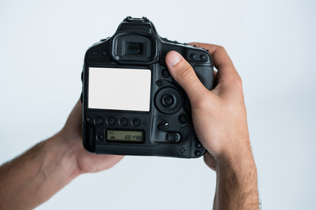Close-up of photographer holding digital camera at studio