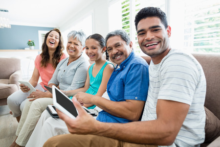 Portrait of multi-generation family using digital tablet in living room at home Stock Photo