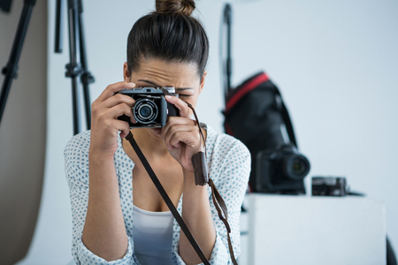 Female photographer with old fashioned camera in studio Stock Photo