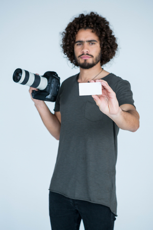 Portrait of male photographer showing visiting card in studio