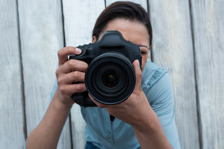Female photographer with digital camera against wooden background Stock Photo