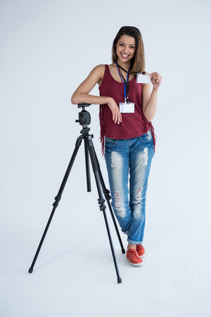 Portrait of female photographer showing identity card in studio