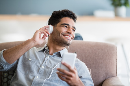 Man listening to music on mobile phone in living room at home
