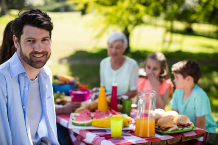 Portrait of smiling man sitting in park while family having meal in background Stock Photo