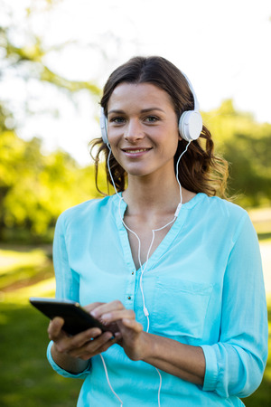Portrait of woman listening music in mobile phone at park Stock Photo