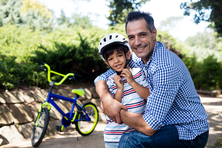 Portrait of father embracing his son in park on a sunny day Stock Photo