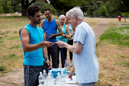 Volunteer registering athletes name for race in park Stock Photo
