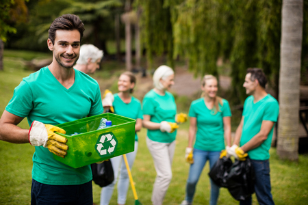 Portrait of recycling team member standing in park