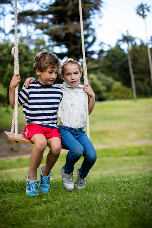 Boy and girl sitting on a swing in park on sunny a day