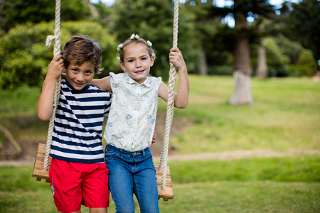 Portrait of boy and girl sitting on a swing in park on sunny a day Stock Photo