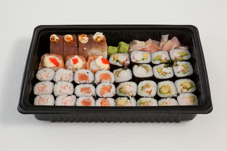 Set of assorted sushi kept in a black box against white background Stock Photo