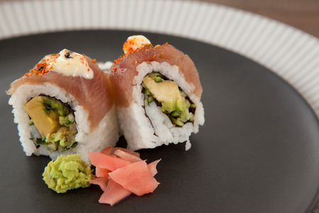 Close-up of two uramaki sushi served in black round plate on wooden table