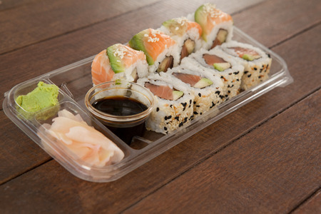 Set of assorted sushi served in a plastic box on wooden table