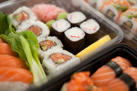 Close-up of assorted sushi set served in plastic boxes