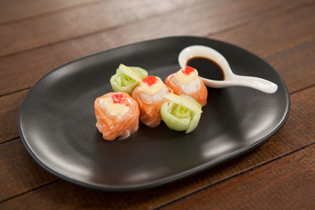 Three nigiri sushi served with soy sauce in black plate on wooden table