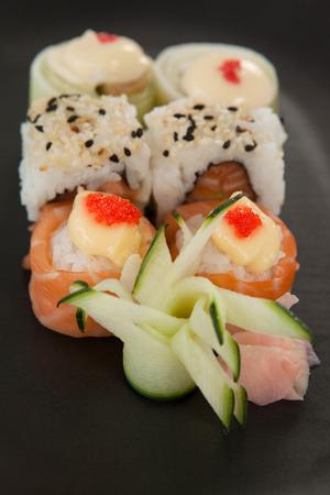 Close-up of uramaki and nigiri sushi served in black plate against white background