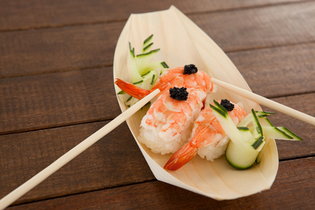 Three nigiri sushi served with chopsticks in wooden boat plate on wooden table