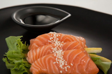Close-up of four sashimi sushi served with soy sauce in black plate Stock Photo