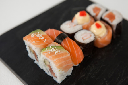 Maki, uramaki and nigiri sushi served in black stone slate on white background Stock Photo