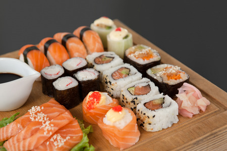 Close-up of assorted sushi set served on wooden tray against black background