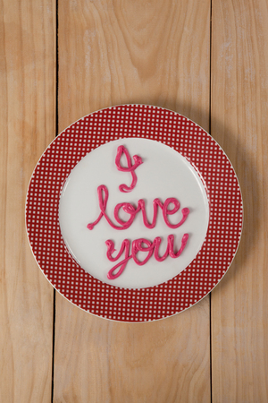 recibo: I love you text written with pink cream on plate on wooden surface Foto de archivo