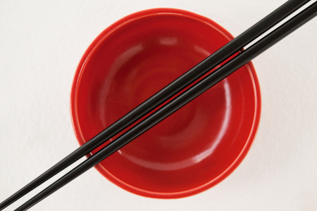 Pair of chopsticks over a bowl against white background Stock Photo