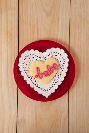 babe: Heart shaped cookie iced with pink cream in text babe on wooden table
