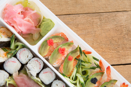Close-up of various sushi rolls with shrimp in plastic tray