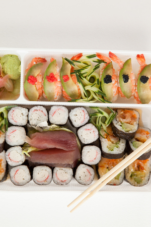 Close-up of assorted sushi set served with chopsticks in white box against white background