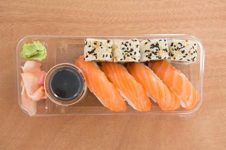 Sushi rolls with salmon in plastic containe