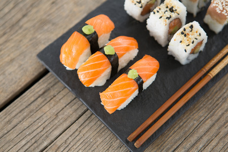 Set of assorted sushi served on black stone slate against wooden background