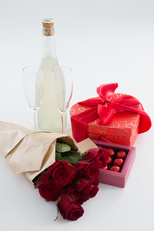 Close-up of gift, chocolate box, roses and champagne bottle on white background