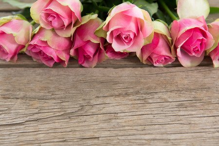 Close-up of bunch of pink roses on wooden background