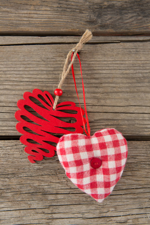 Close-up of two heart shape decoration hanging on wooden plank Stock Photo