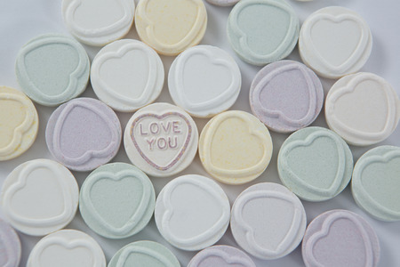 western script: Close-up of heart shape confectionery with text I love you