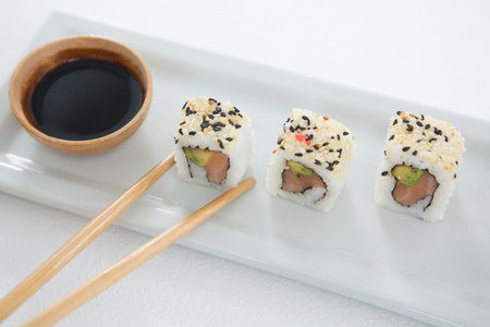 Sushi on tray with sauce and chopsticks