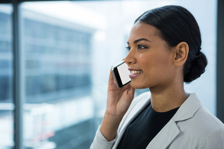 Businesswoman talking on mobile phone in office Stock Photo