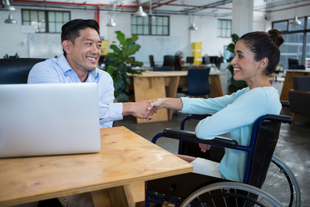Businessman shaking hands with disabled colleague in office Imagens