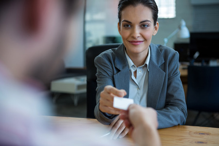 visiting card: Business executive giving visiting card to man during interview in office Stock Photo