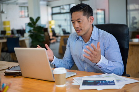 Gefrustreerde directeur die laptop in bureau bekijkt Stockfoto