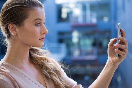 Beautiful woman taking a selfie on mobile phone