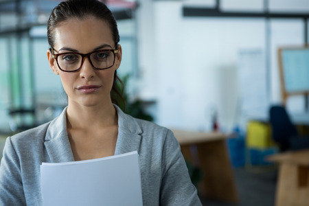 Portrait of businesswoman holding document in office Stock Photo