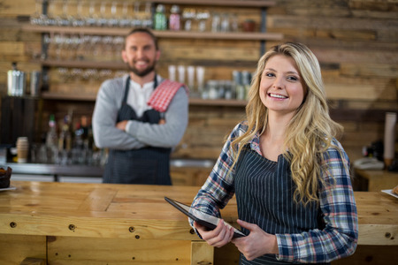Portrait of smiling waitress standing with digital tablet in café