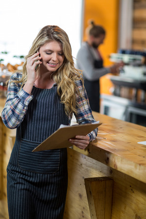 Smiling waitress looking at clipboard while talking on mobile phone in café