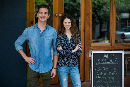 Portrait of smiling man and woman standing outside café beside the menu board Stock Photo