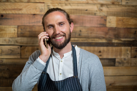 Portrait of smiling waiter talking on mobile phone against wooden wall in cafe
