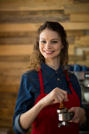 Waitress using a tamper to press ground coffee into a portafilter in café Stock Photo