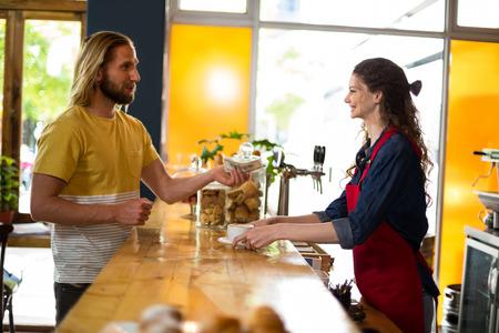 tomando refresco: Smiling customer paying bill by cash at counter in café Foto de archivo