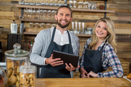 confident business woman: Portrait of smiling waiter and waitress using digital tablet at counter in cafe